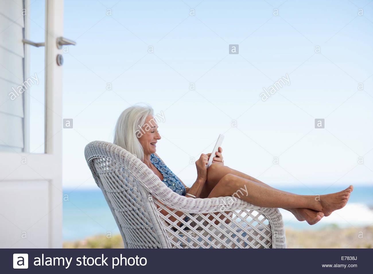 Mujer mayor utilizando digital comprimido en silla Imagen De Stock