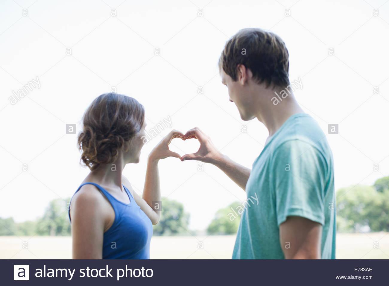 Pareja sonriente usando las manos para hacer con forma de corazón Imagen De Stock