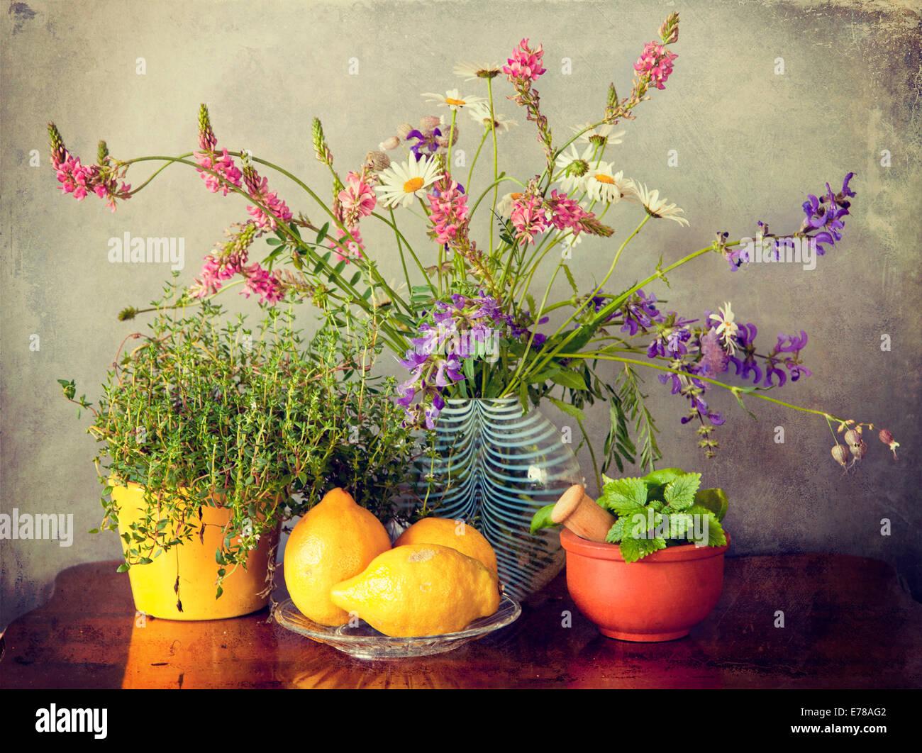 Jardín de hierbas, flores del campo en jarrón y frutas de limón. Grunge textura y Instagram-como Imagen De Stock