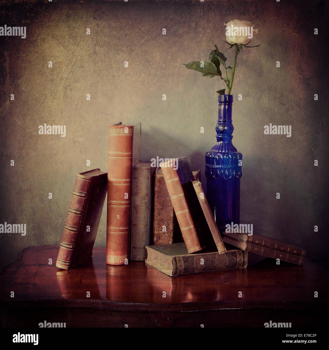 Todavía la vida interior, la composición de libros antiguos en una mesa de madera y una sola rosa rosa en una botella Foto de stock