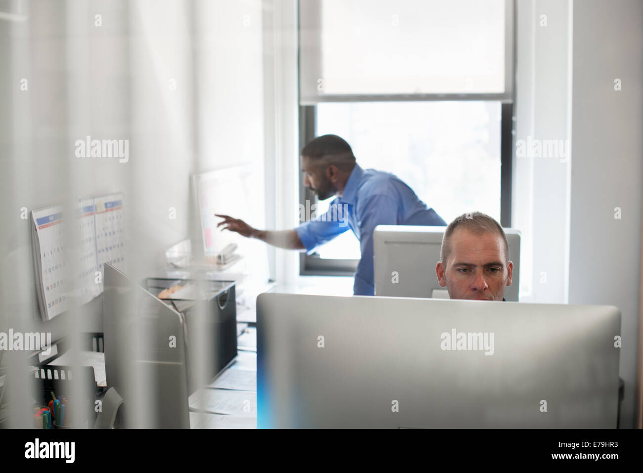 Un hombre sentado en un ordenador, y otro que trabaja en una pared planificador gráfico. Imagen De Stock