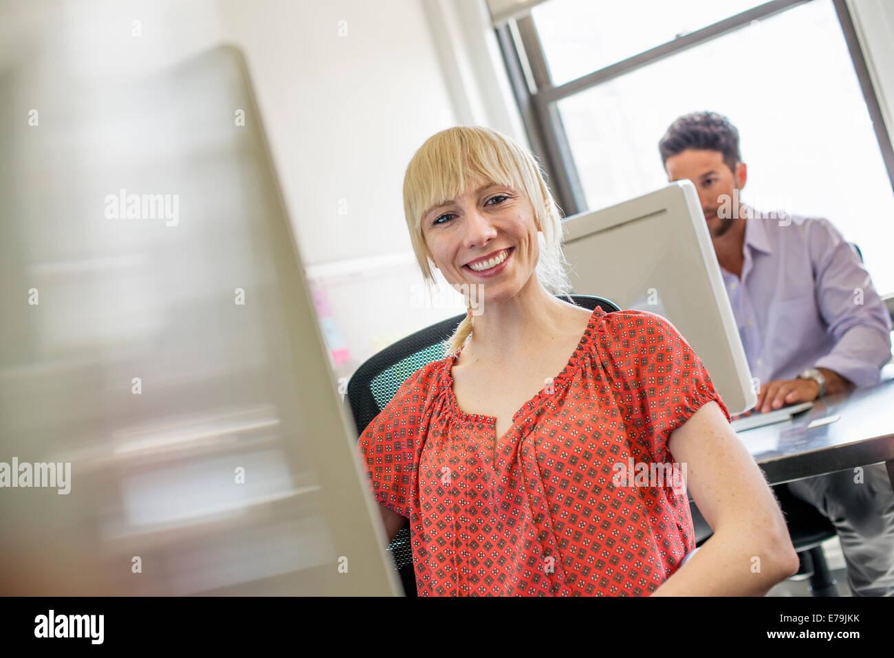 Vida de oficina. Dos personas sentadas en los escritorios usando computadoras. Imagen De Stock