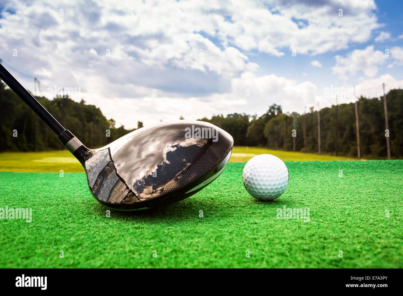 Close-up de una bola de golf y un campo de golf de madera en un driving range Imagen De Stock