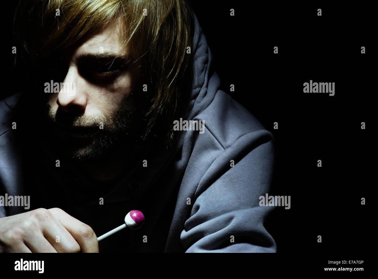 Un hombre tranquilo sosteniendo un lollipop, cabeza y hombros. Imagen De Stock