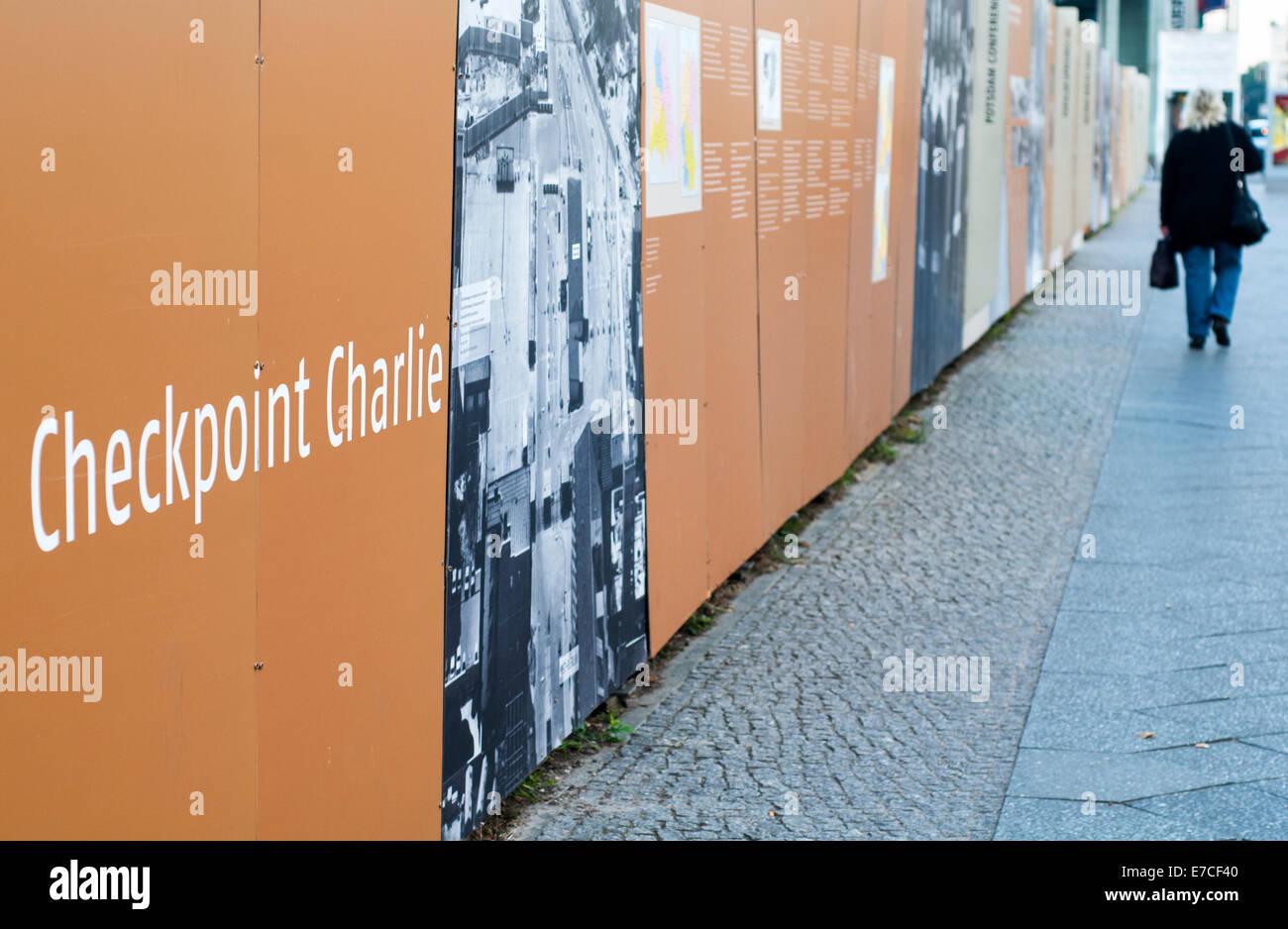 Mujer caminando por una exposición al aire libre, cerca de Checkpoint Charlie, en Berlín, Alemania Imagen De Stock