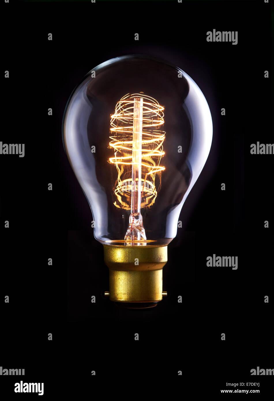 Un clásico Edison lámpara con un filamento de bucle. Encendido. Imagen De Stock