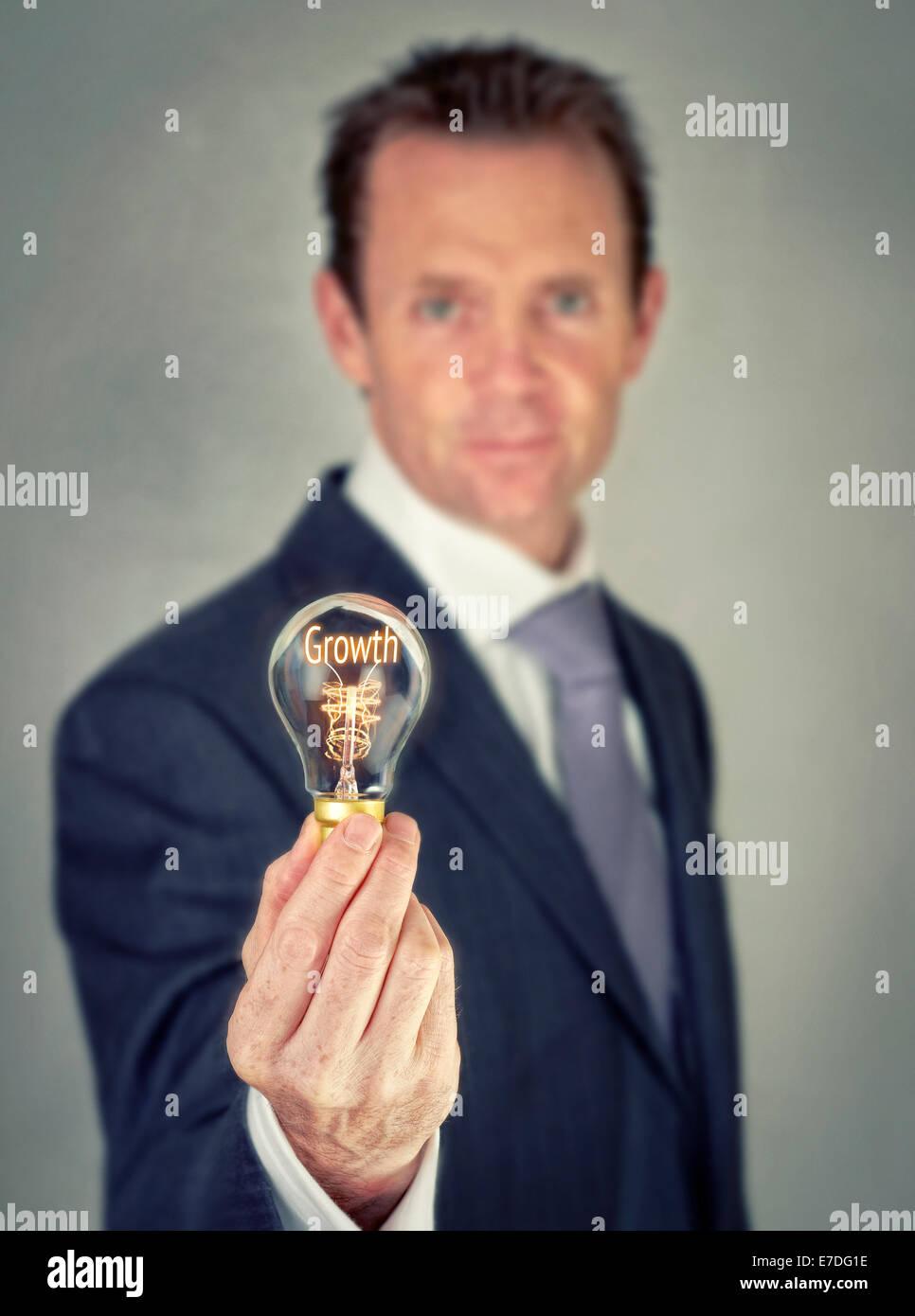 Empresario sosteniendo un concepto bombilla iluminada con la palabra crecimiento. Imagen De Stock