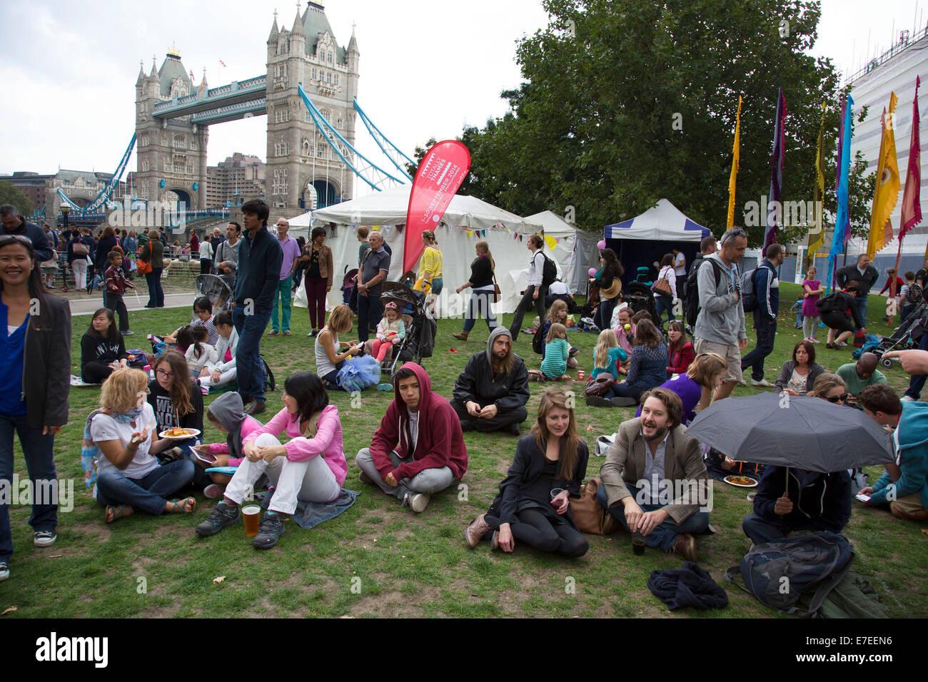 Personas que se reúnen para pasar el rato, escuchan bandas y otras actividades en la aldea de Blue Ribbon. Thames Festival Londres Reino Unido. Foto de stock