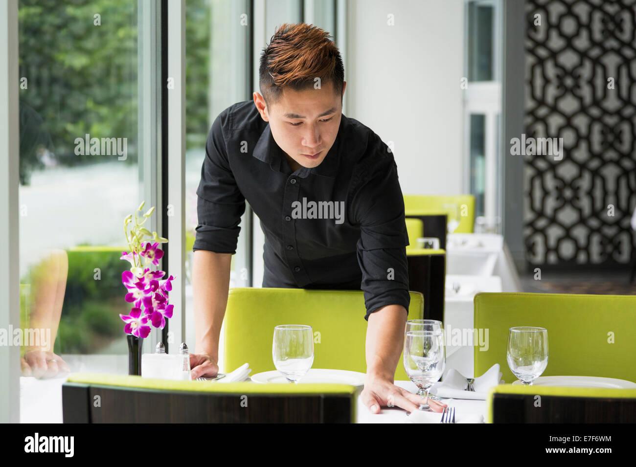 Tabla de configuración de camarero asiática en el restaurante Foto de stock