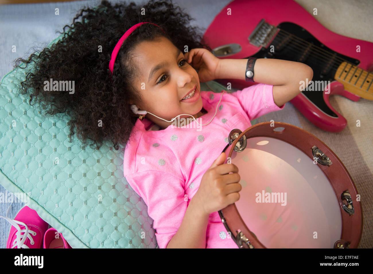 African American Girl escuchando música celebración pandereta Foto de stock