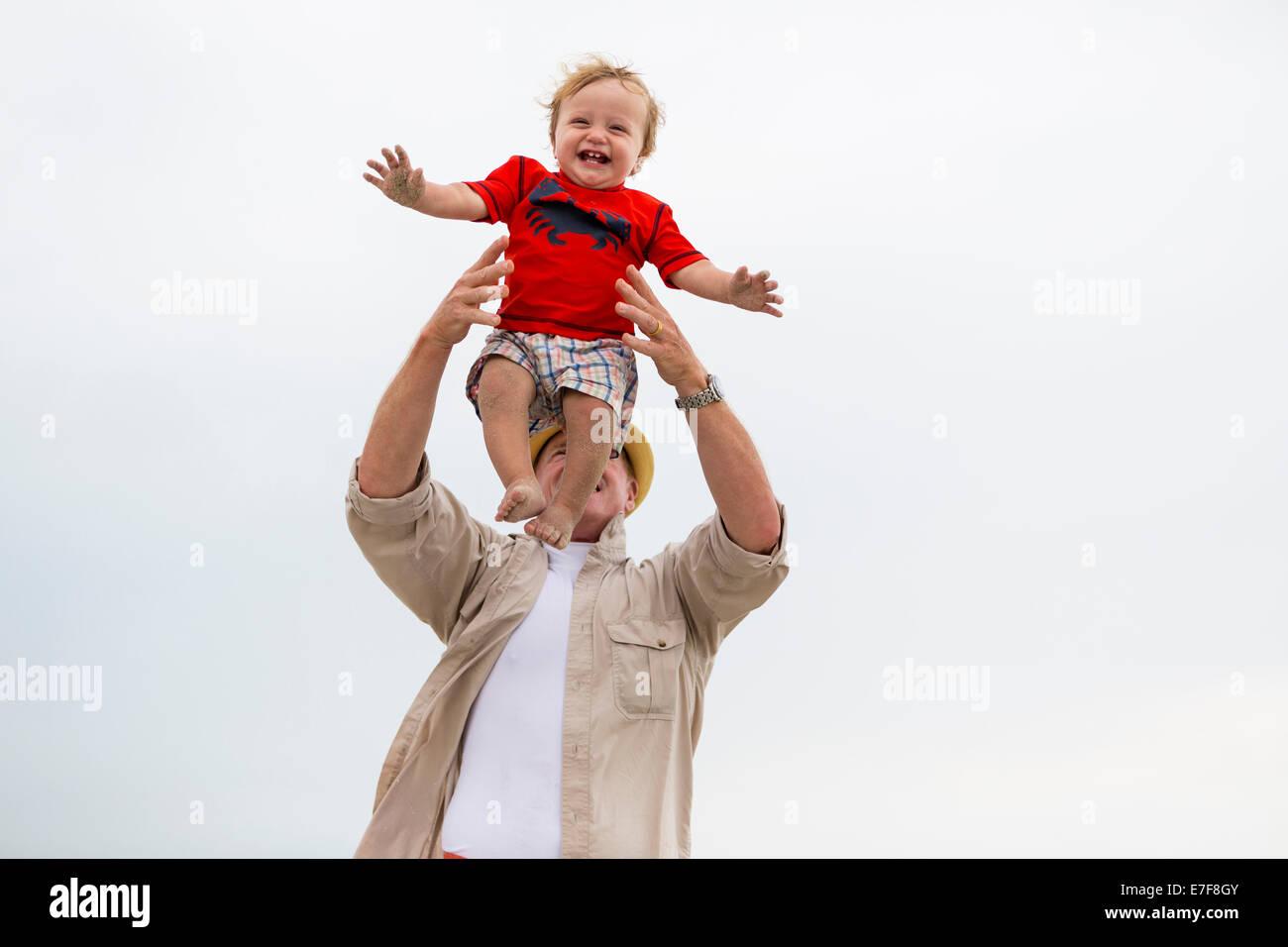 Hombre caucásico jugando con su nieto en el exterior Foto de stock