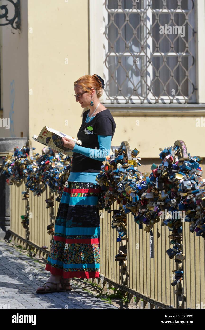 Un agente del Segway principales contra la barandilla de un puente cubierto con una serie de candados cerrados, Praga, República Checa. Foto de stock