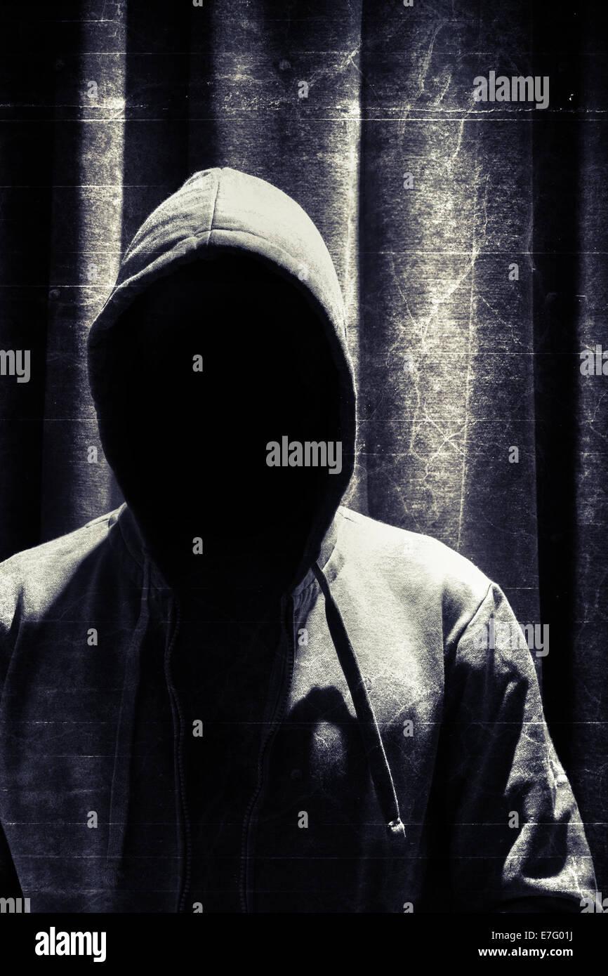 Retrato de incógnito hombre bajo el capó con Grunge antecedentes cortina Imagen De Stock