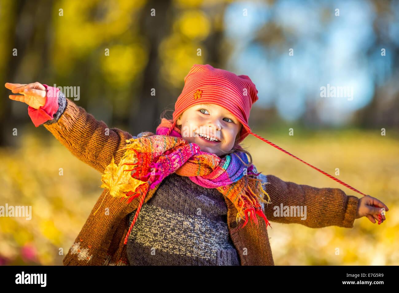 Niña feliz jugando en el parque de otoño Imagen De Stock