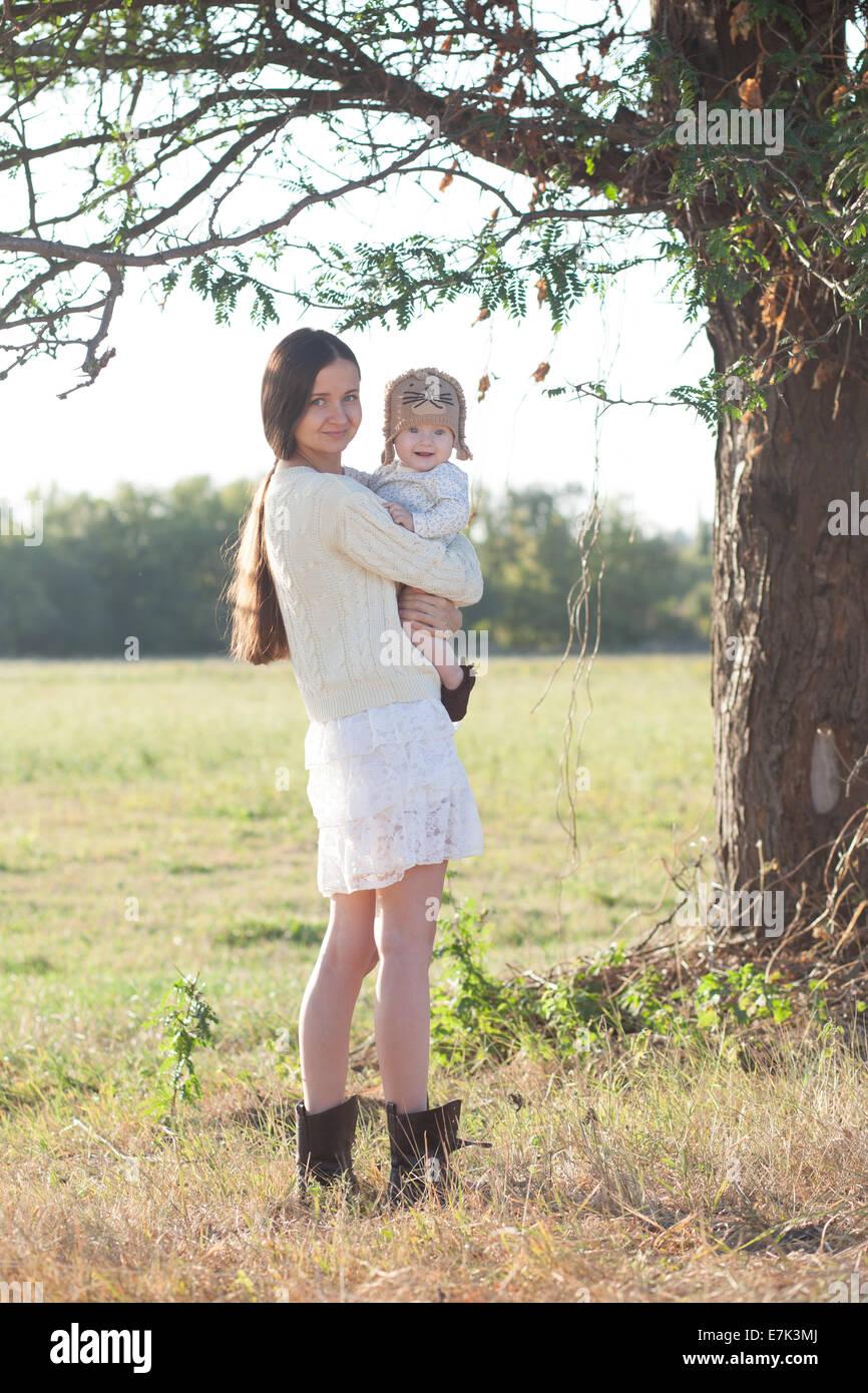 El bebé y la madre paseando por paisajes suburbanos Imagen De Stock