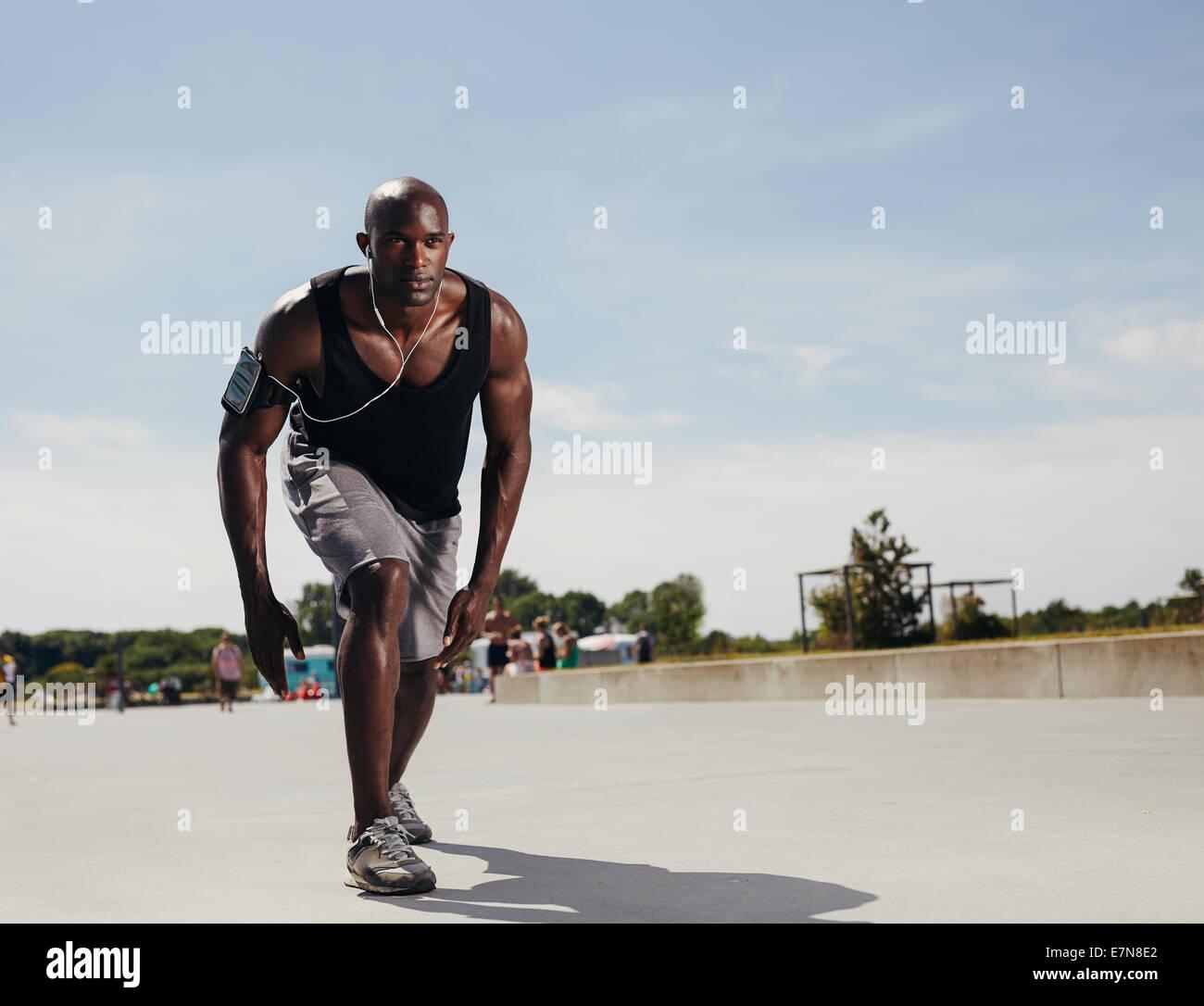 Colocar joven en su marca para empezar a funcionar. Determinado deportista al aire libre. Varón africano muscular Imagen De Stock