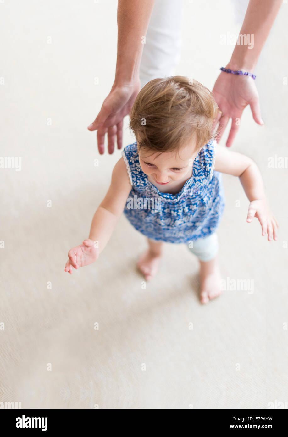 Ayudar a la madre a la hija pequeña (18-23 meses) con sus primeros pasos Foto de stock