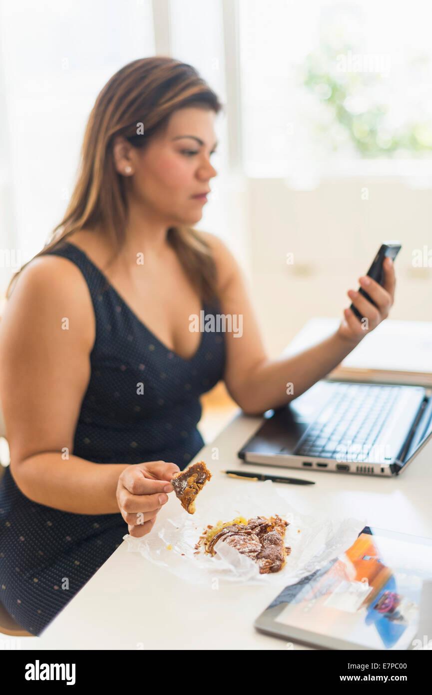 Mujer comiendo croissant y a través de teléfono móvil en la oficina Foto de stock