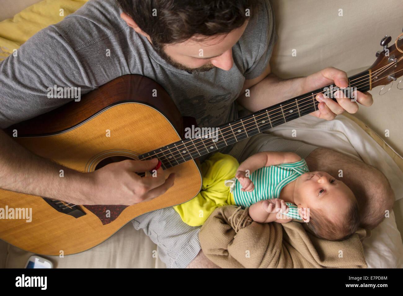 Padre tocando la guitarra para su hija recién nacida Foto de stock