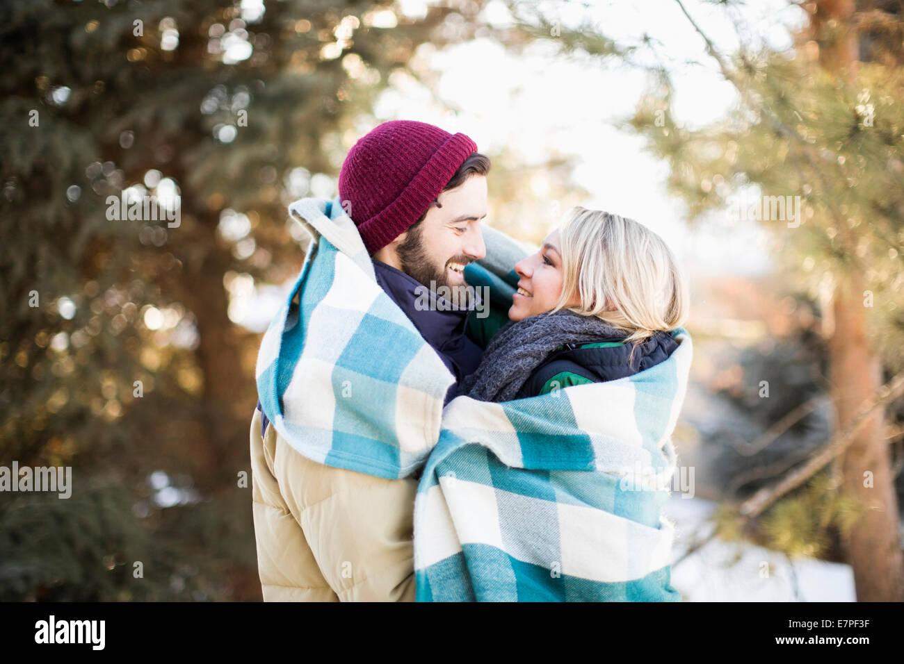 Estados Unidos, Utah, Salt Lake City, pareja envuelta en una manta abrazando al aire libre Imagen De Stock