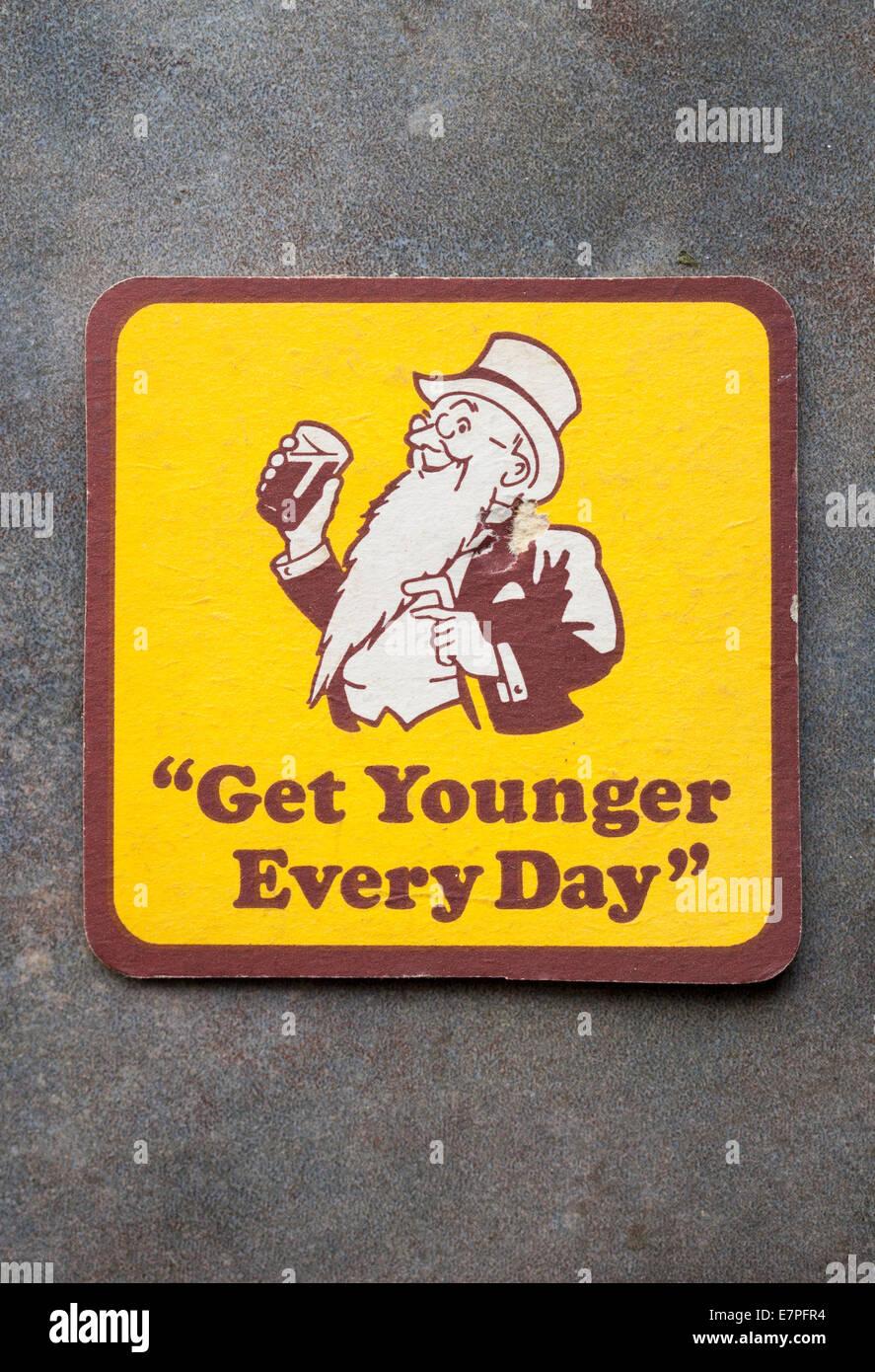 Cervecería Vintage Beermat publicidad de cerveza local 'Youngs' con el lema 'Obtener menores cada Imagen De Stock