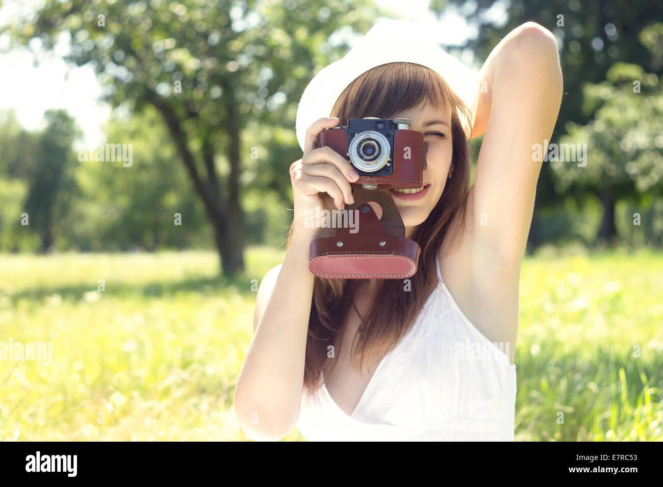Young Pretty Woman posando con cámara de película antigua en verano park. Niña de sombrero blanco Imagen De Stock