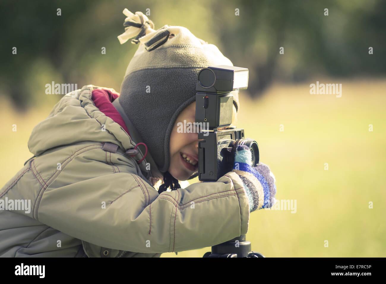 Cute niño pequeño disparar una fotografía en otoño park Imagen De Stock