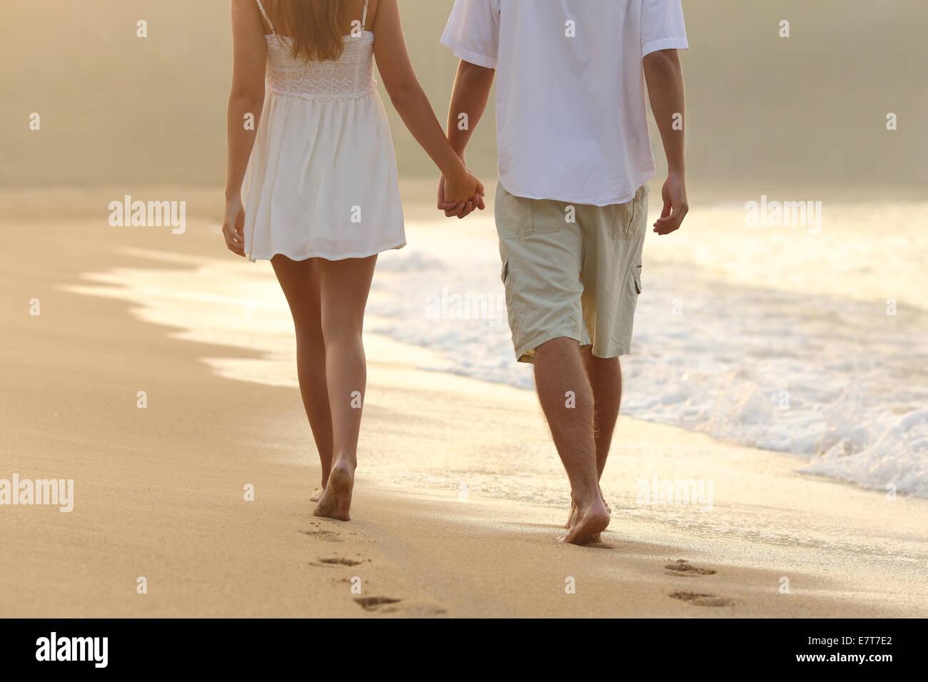 Vista posterior de una pareja dando un paseo tomados de las manos en la playa al amanecer. Imagen De Stock