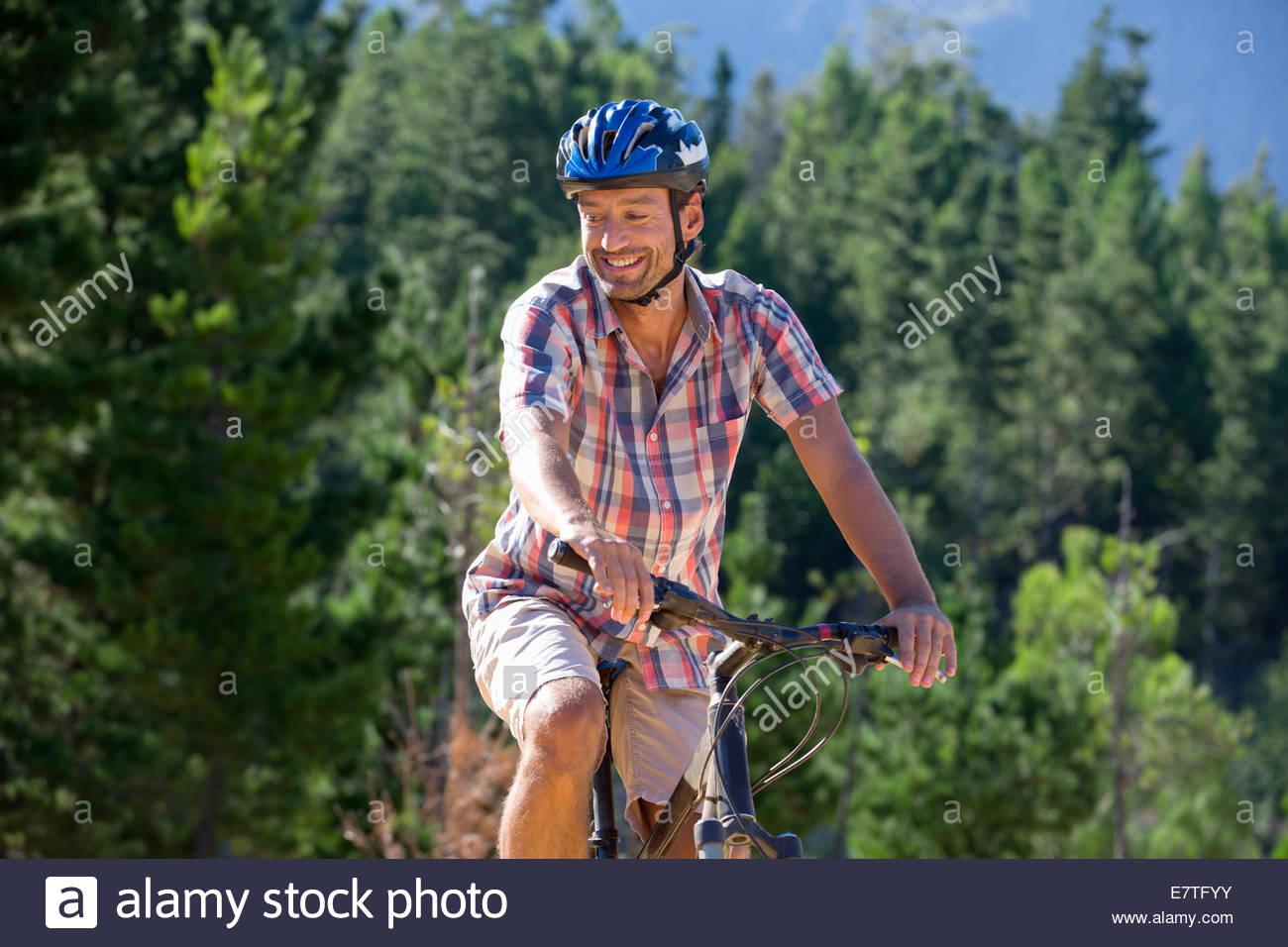 Hombre montando en bicicleta de montaña en el bosque Imagen De Stock