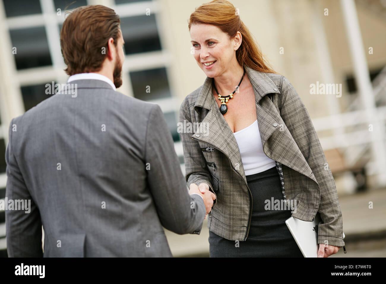 Dos personas de negocios saludándonos Imagen De Stock