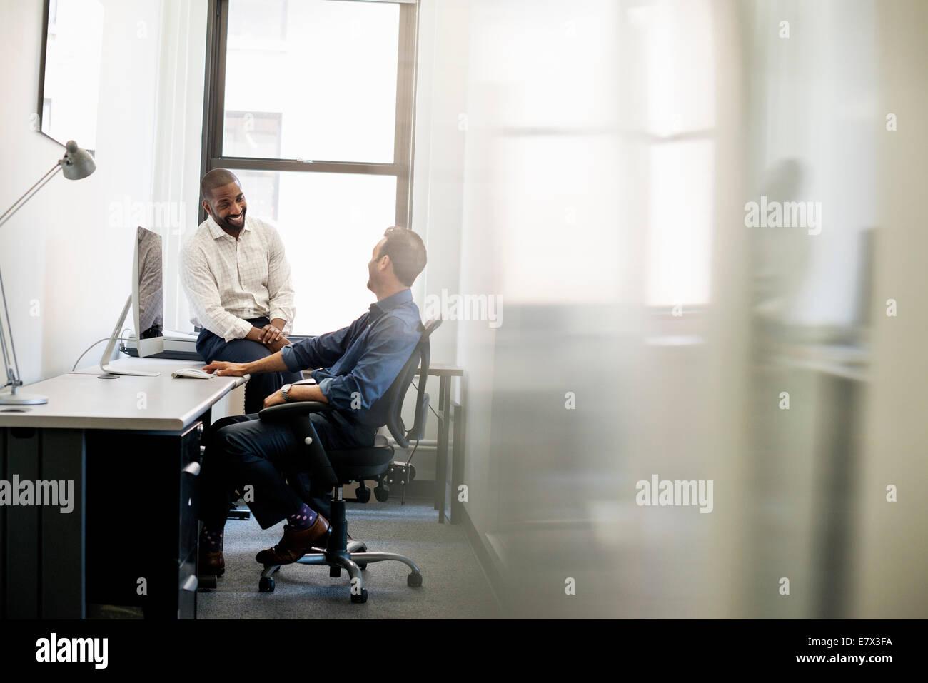 Vida de oficina. Un hombre inclinado hacia atrás en una silla de oficina hablando con un colega sentado en el borde Foto de stock