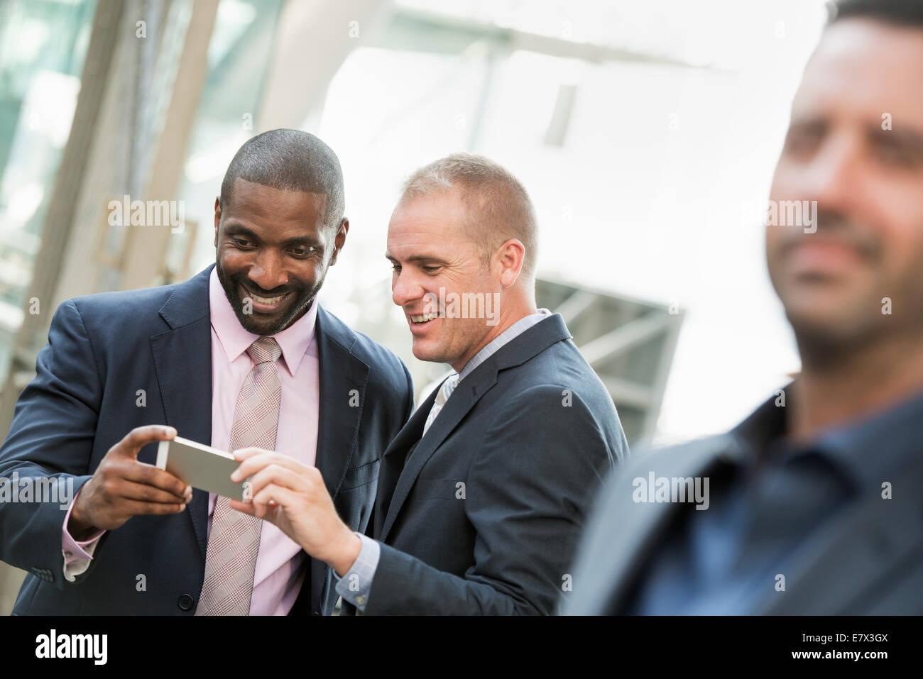 Dos empresarios controlar un teléfono y riendo, un hombre en el primer plano. Imagen De Stock