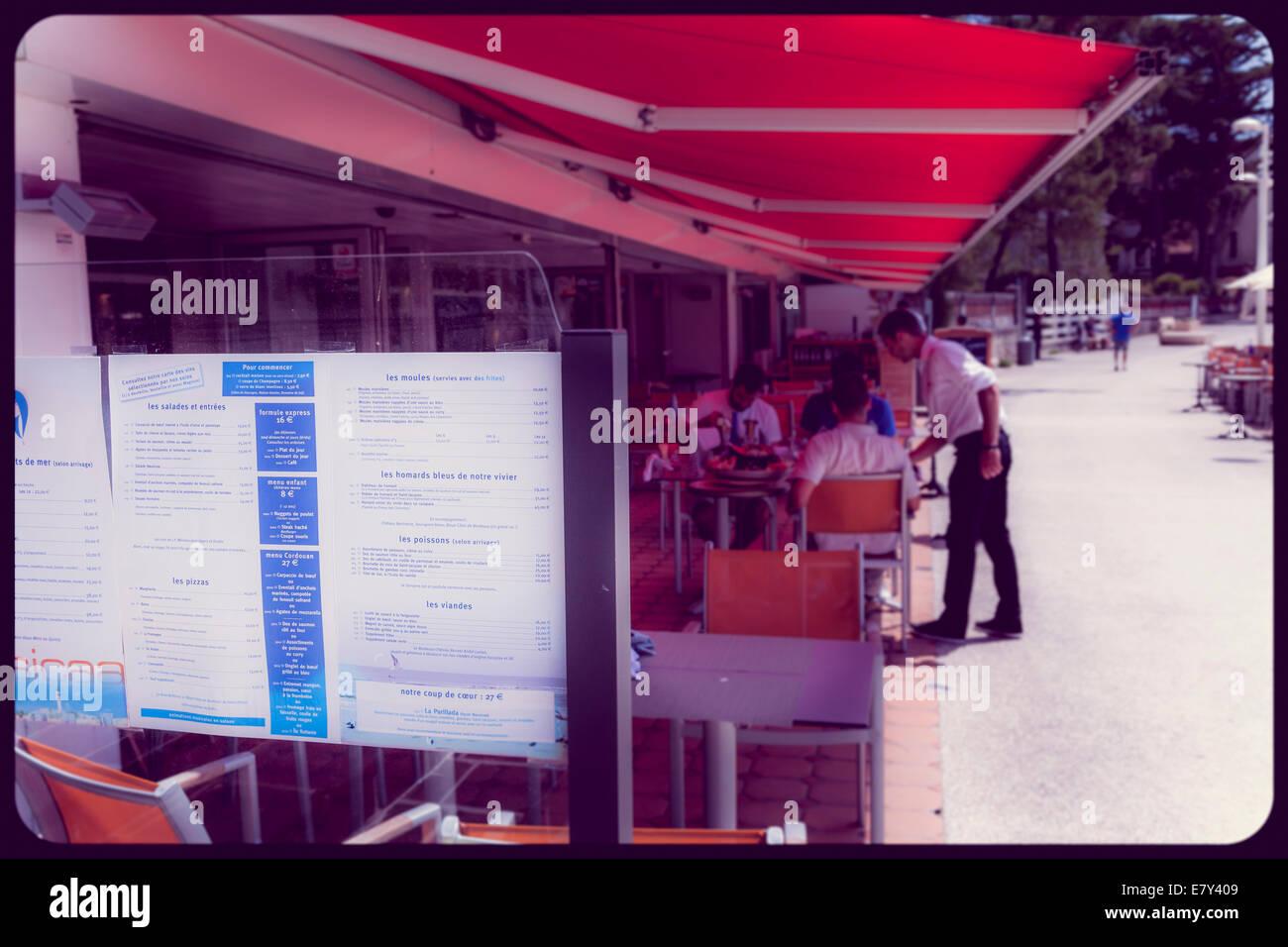 Menú en el restaurante Promenade en sunshine borrosa con clientes y camareros. Imagen De Stock
