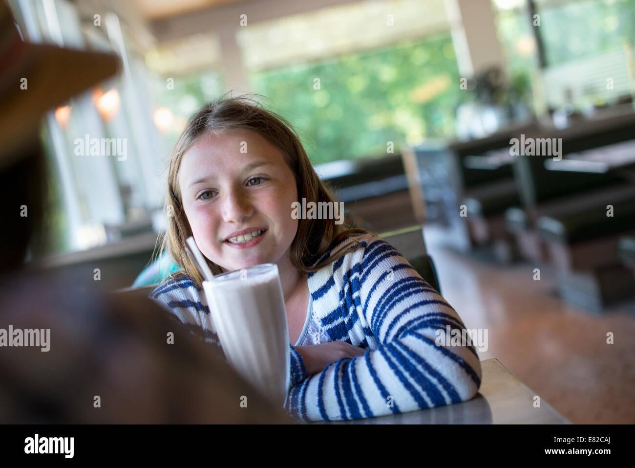 Una joven con una gran sacudida de leche en una mesa de comedor. Foto de stock