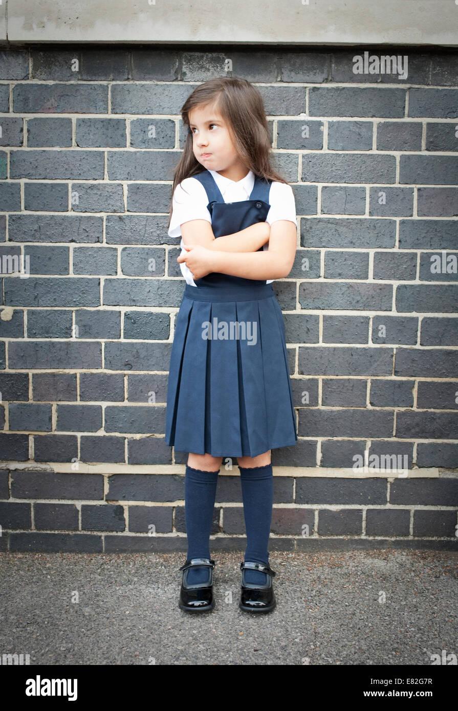 Retrato de niña en el patio mirando malhumorado con brazos cruzados Foto de stock