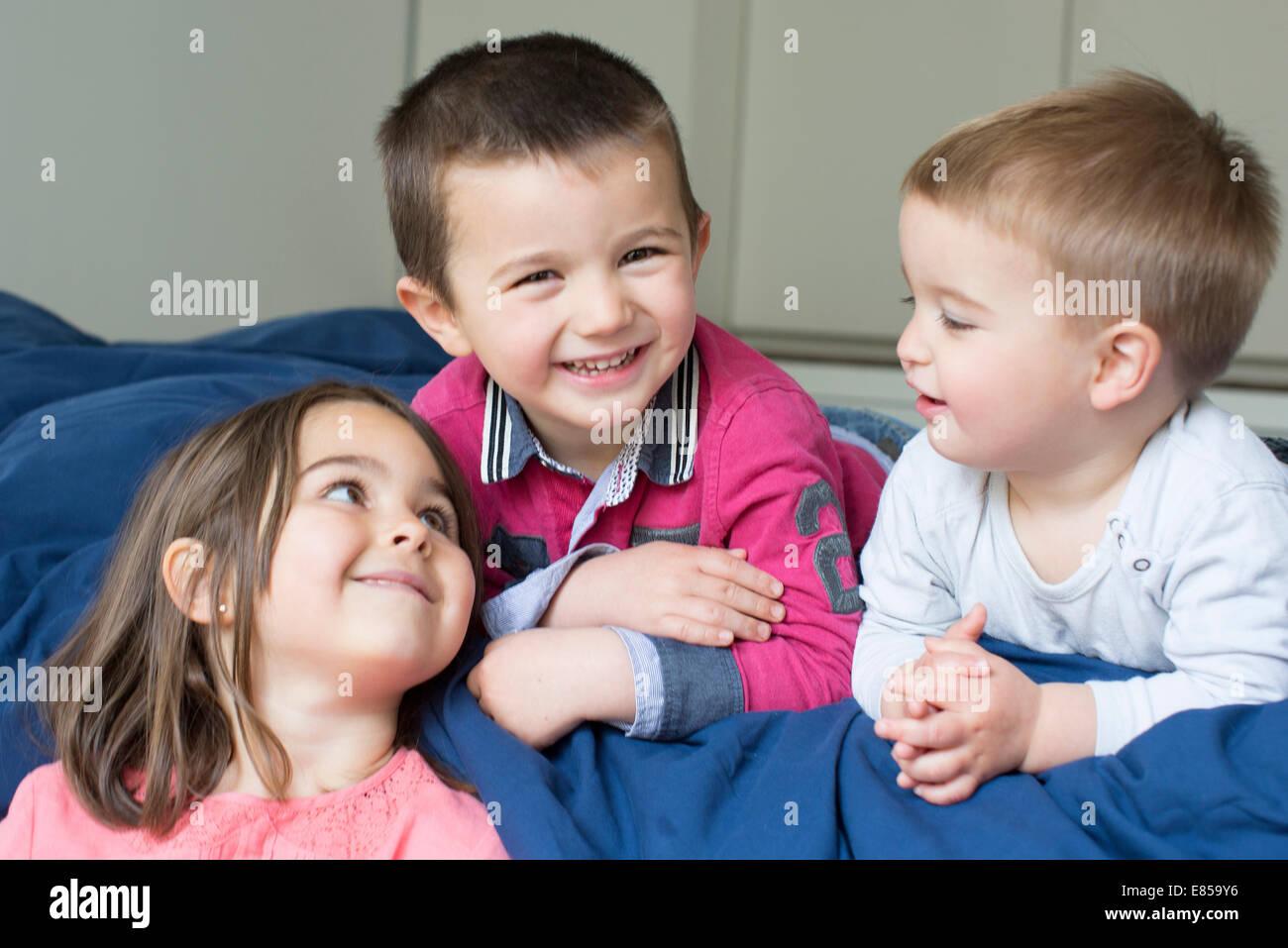 Hermanos jóvenes relajándose juntos en la cama Foto de stock