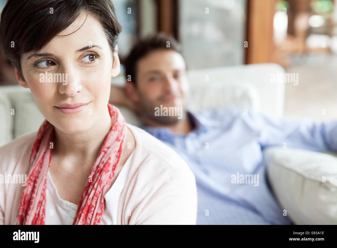 Mujer mirando lejos dreamily, hombre relajante en segundo plano. Imagen De Stock