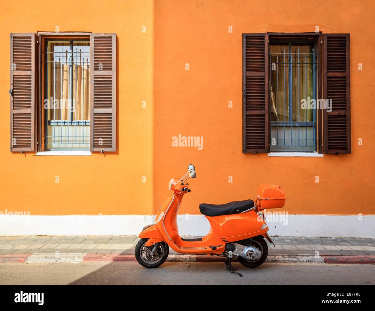 Scooter aparcada por el bordillo contra el edificio naranja en Tel Aviv, Israel Imagen De Stock