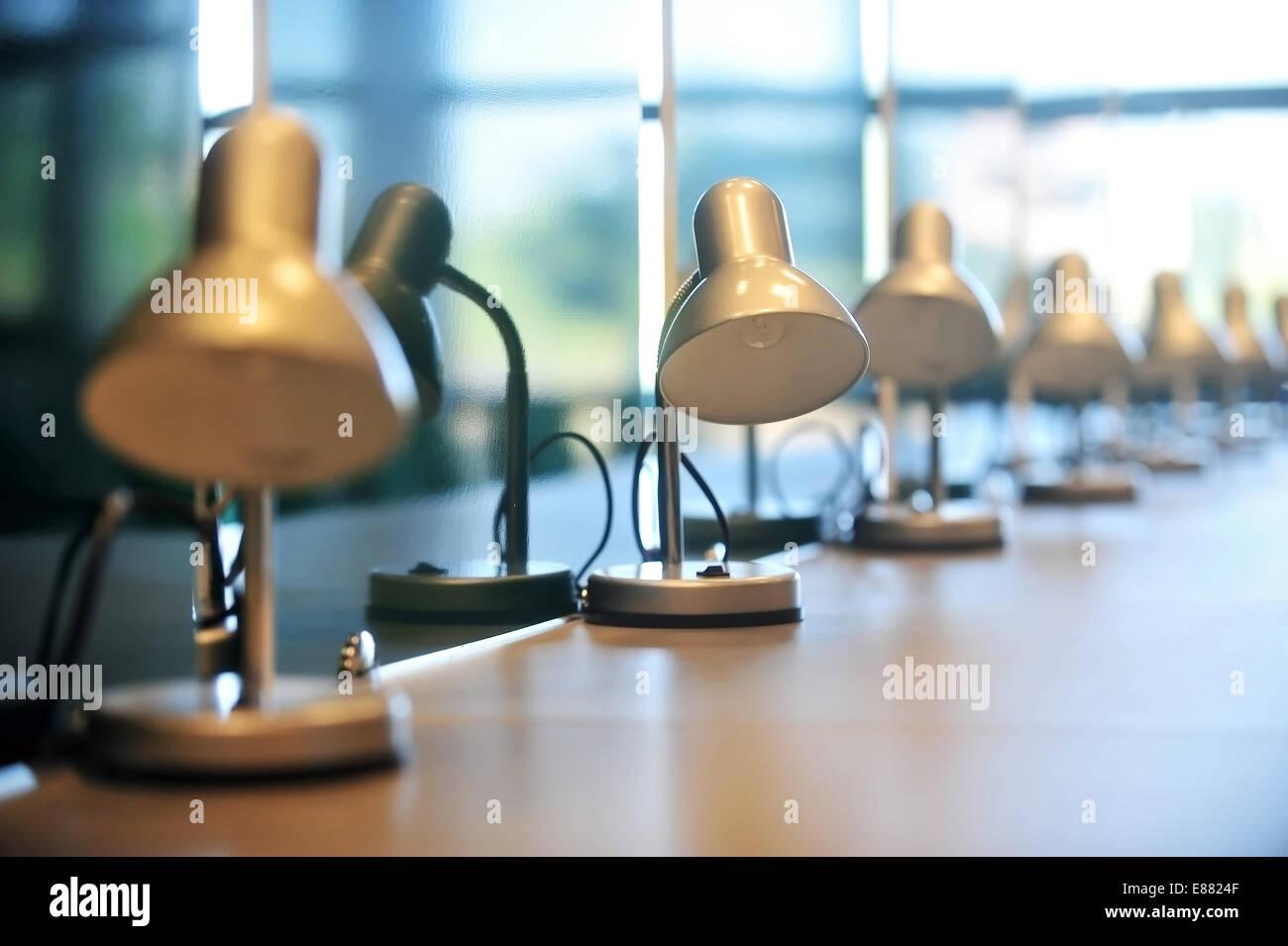 Varias lámparas de lectura de la biblioteca en una fila sobre un escritorio Imagen De Stock