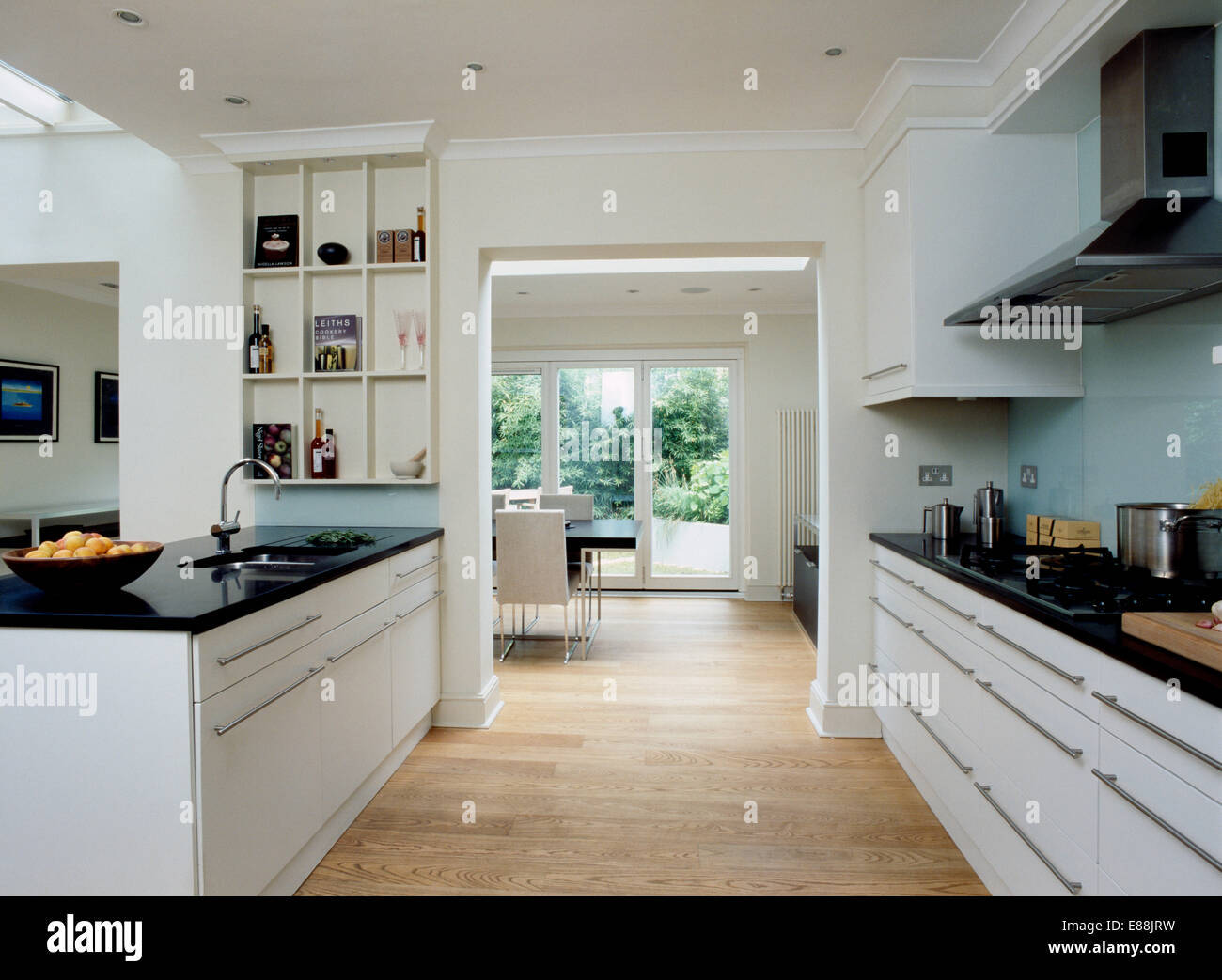 Suelos de madera en la gran cocina moderna con puerta al comedor y encimeras de granito negro sobre blanco unidades