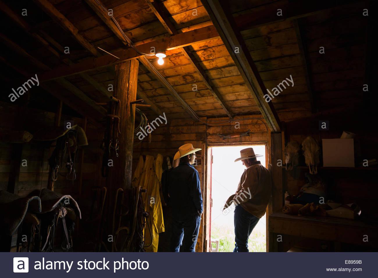 Los rancheros hablando en el granero puerta Imagen De Stock
