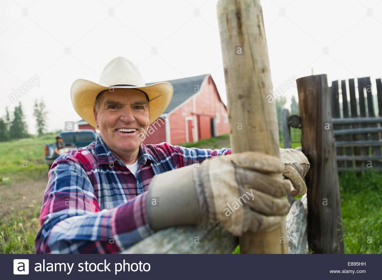 Retrato del ranchero sonriente apoyado en poste de cerca Imagen De Stock