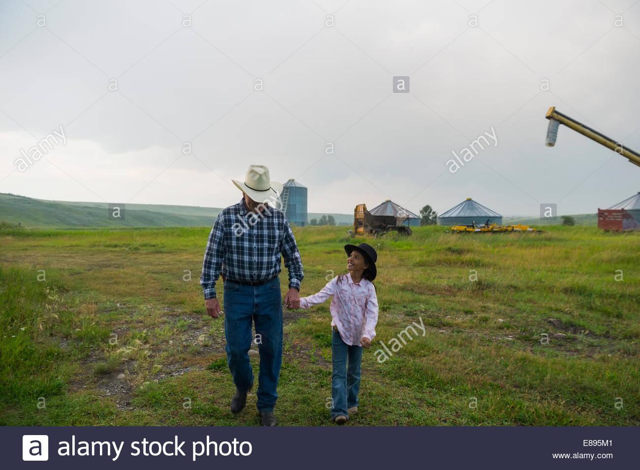 Abuelo y nieta caminando en la granja Imagen De Stock