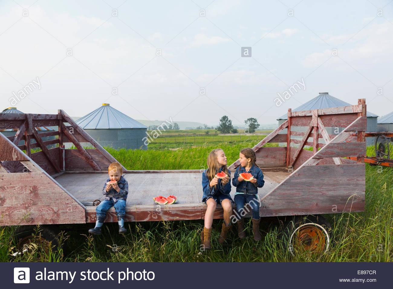 Las niñas y niño comiendo sandía en la granja Imagen De Stock