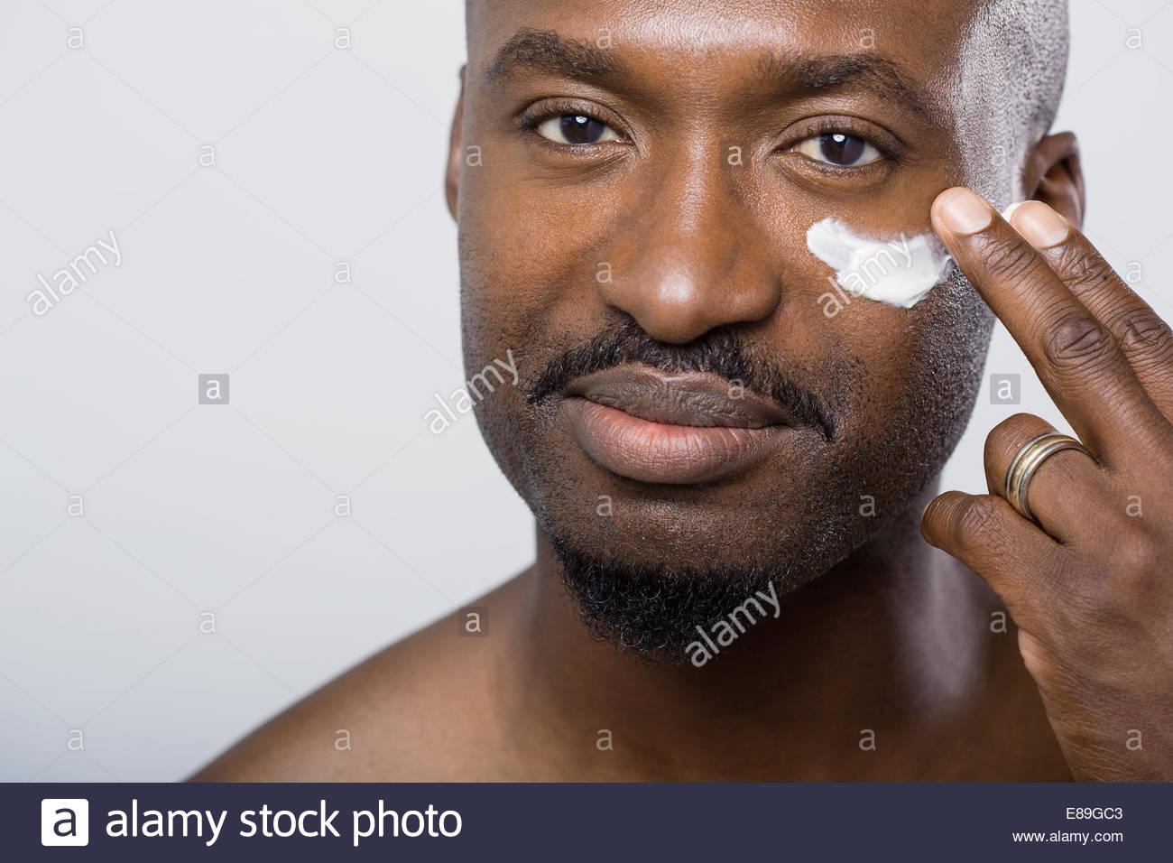 Cerca del hombre aplicar crema humectante bajo ojo Imagen De Stock
