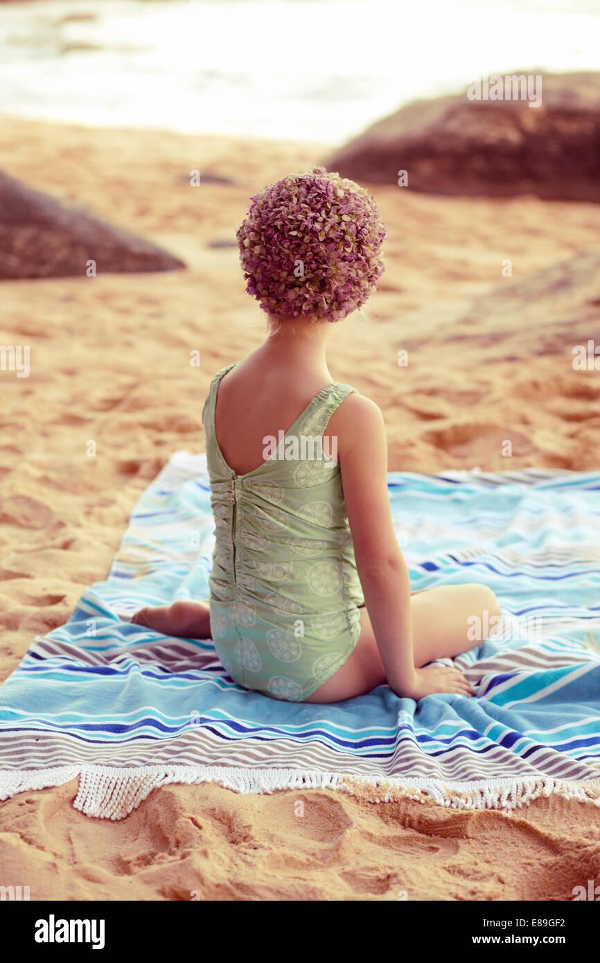Chica en swimcap sentado en playa manta Imagen De Stock