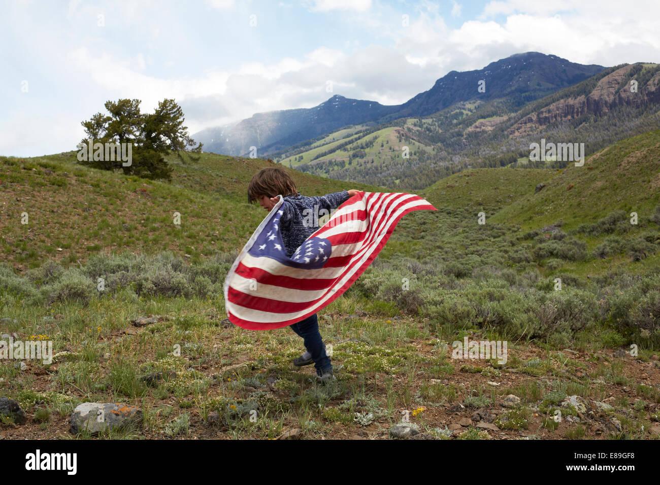 Niño sosteniendo la bandera americana en colinas Imagen De Stock