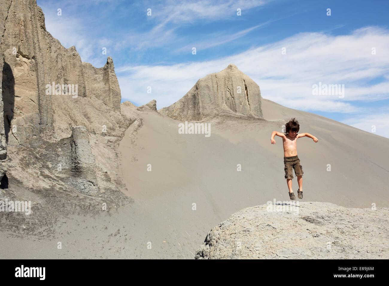 Chico saltando sobre dunas de arena Imagen De Stock