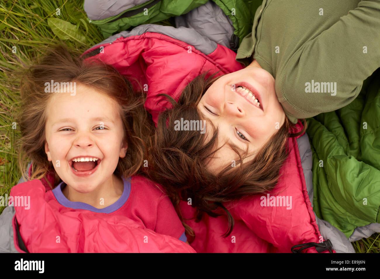 Laughing kids sentando en sacos de dormir Imagen De Stock