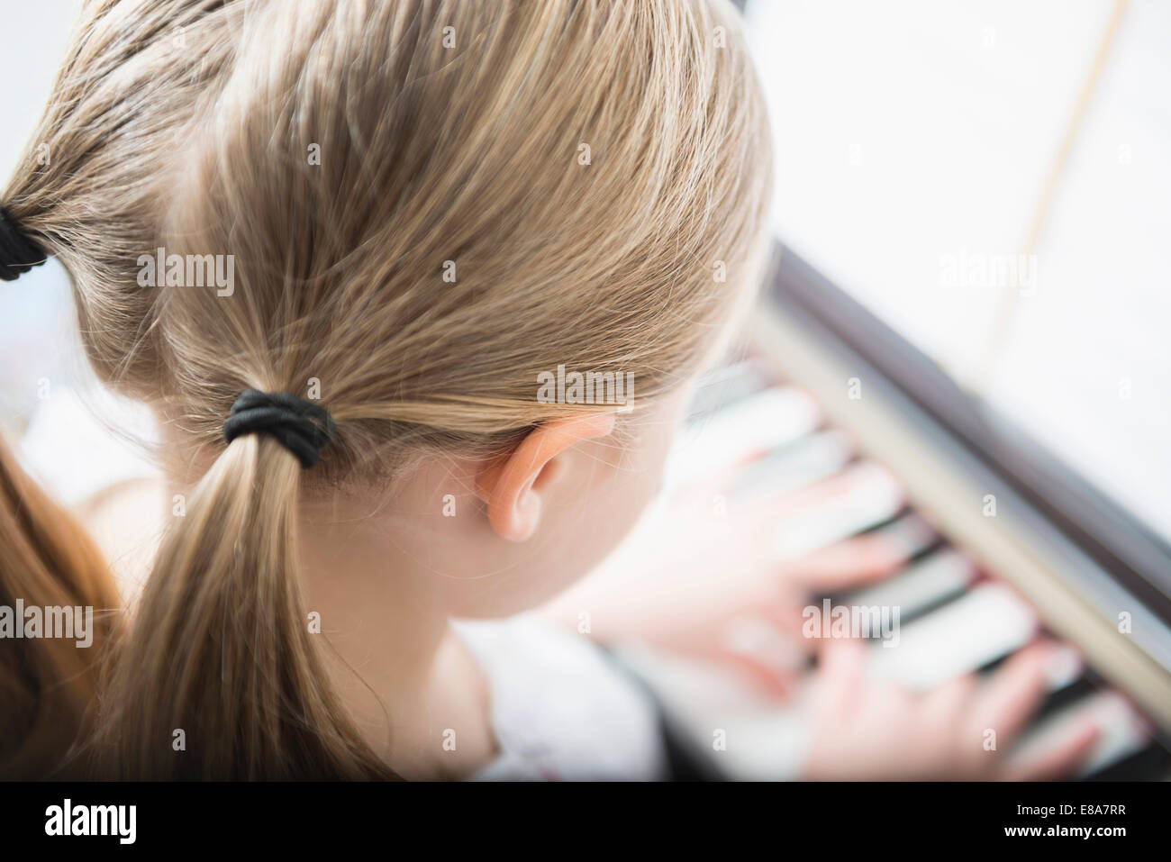 Niña de 6 años que practica tocando el piano Imagen De Stock